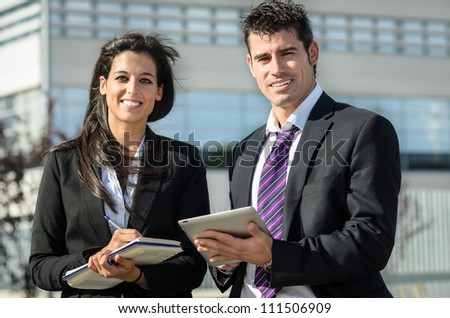 Business people outside. Business man and woman smiling and taking notes in digital tablet and notebook outdoors.
