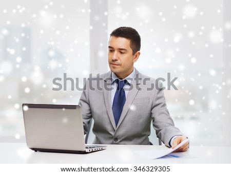 business, people, paperwork and technology concept - businessman with laptop computer and papers working in office over snow effect