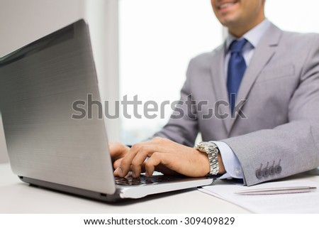 business, people, paperwork and technology concept - close up of smiling businessman with laptop computer and papers working in office - stock photo