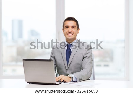 business, people, paperwork and technology concept - smiling businessman with laptop computer and papers working in office - stock photo