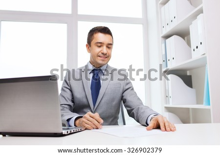 business, people, paperwork and technology concept - smiling businessman with laptop computer and papers working in office