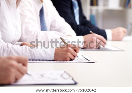 Business people participating in a seminar and taking notes - stock photo