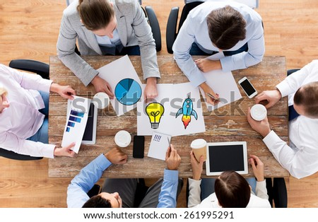 business, people, planning and team work concept - close up of creative team with papers and gadgets meeting and drinking coffee in office - stock photo