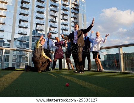 Business people playing golf in a corporate environment - stock photo