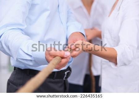 Business people playing tug-of-war - stock photo