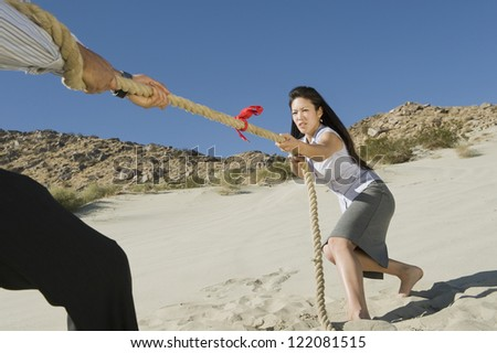Business people playing tug of war in desert - stock photo
