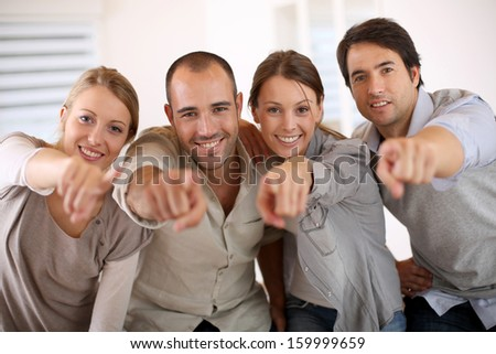 Business people pointing at camera - stock photo