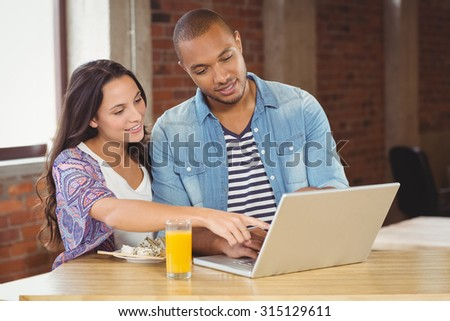 Business people pointing towards laptop while standing in creative office