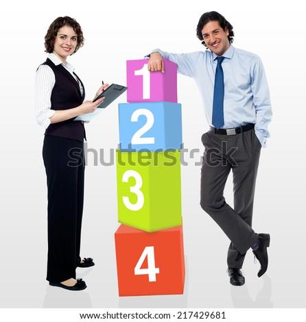 Business people posing beside number blocks - stock photo