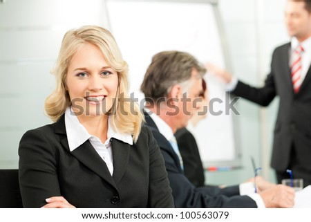 Business people - presentation within a team, a colleague is standing on the flipchart, one female colleague is looking into the camera - stock photo
