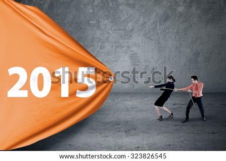 Business people pulling a big banner of number 2015 - stock photo