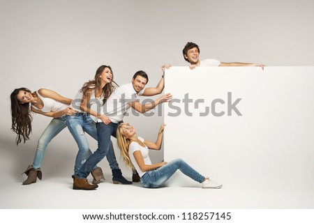 Business people pulling an empty white board - stock photo