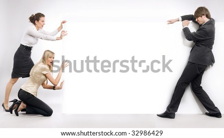 Business people pushing an empty white board - stock photo