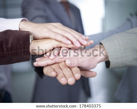 business people putting hands together to show unity.