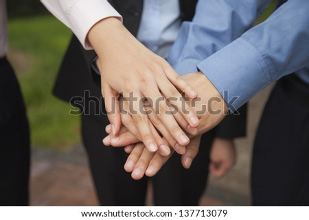Business people putting their hand together as sign of team working