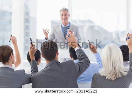 Business people raising their arms during meeting in office - stock photo