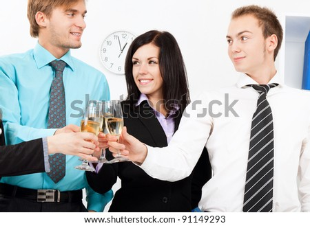 Business people raising toast with champagne and happy smile at office looking at camera. - stock photo