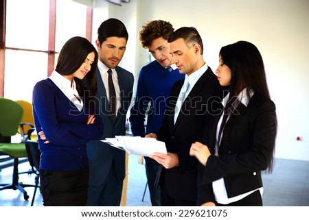 Business people reading a document together in the office