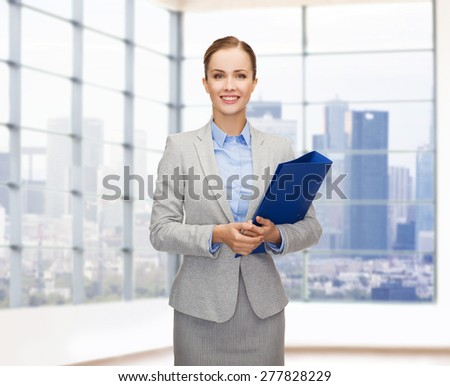 business, people, real estate and sale concept - smiling young businesswoman holding folder over office or empty city apartment background - stock photo