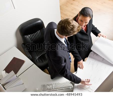 Business people reviewing blueprints together - stock photo
