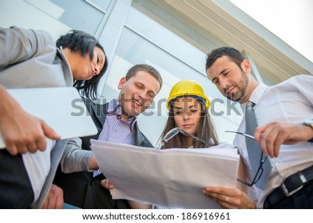Business people reviewing construction plans in front of building - stock photo