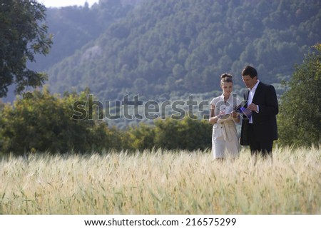 Business people reviewing paperwork in rural field