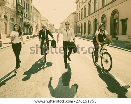 Business people riding on bikes and running in city - retro style photograph - stock photo