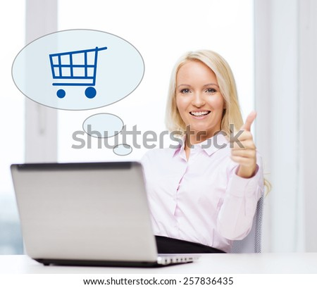business, people, sale, gesture and technology concept - smiling businesswoman or student showing thumbs up with laptop computer and shopping trolley in text bubble at office - stock photo