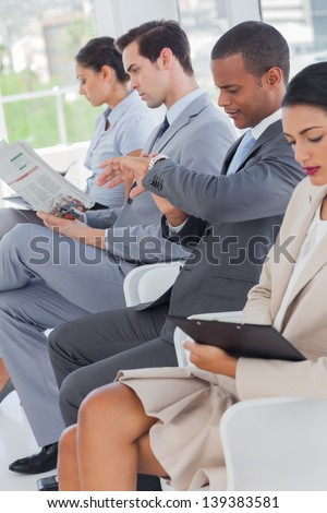 Business people sat in line in a waiting room - stock photo