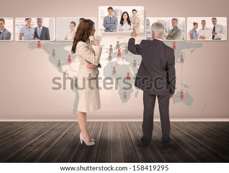 Business people selecting digital interface together showing coworkers - stock photo