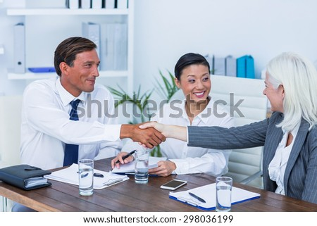 Business people shake hands during meeting in office - stock photo