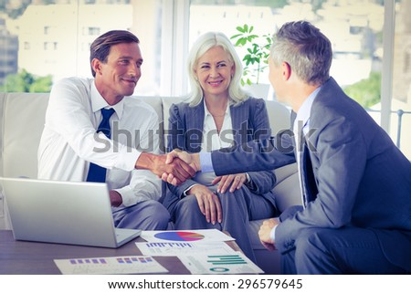 Business people shake hands on couch in office - stock photo