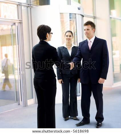 Business people shaking hand in the entrance of the office building.