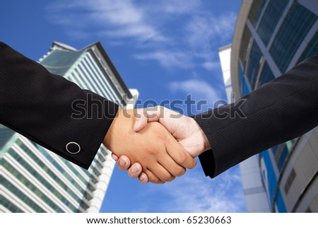 business people shaking hands against blue sky and modern building - stock photo