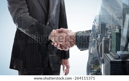 Business people shaking hands against city skyline - stock photo