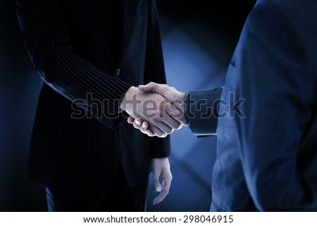 Business people shaking hands against dark grey room - stock photo
