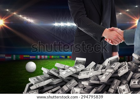 Business people shaking hands against football pitch with lights and flags - stock photo