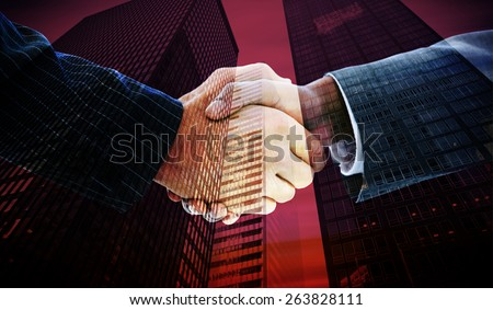 Business people shaking hands against low angle view of skyscrapers - stock photo