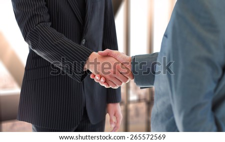 Business people shaking hands against room with large window looking on city - stock photo