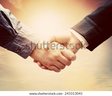 Business people shaking hands against sunny sky background in vintage mood. Conceptual handshake - stock photo