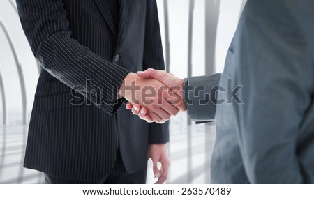 Business people shaking hands against white room with large window overlooking city - stock photo