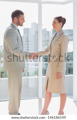 Business people shaking hands and smiling in a large office - stock photo