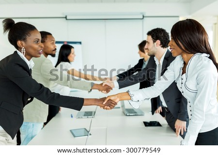 Business people shaking hands before sitting down to a conference table - stock photo