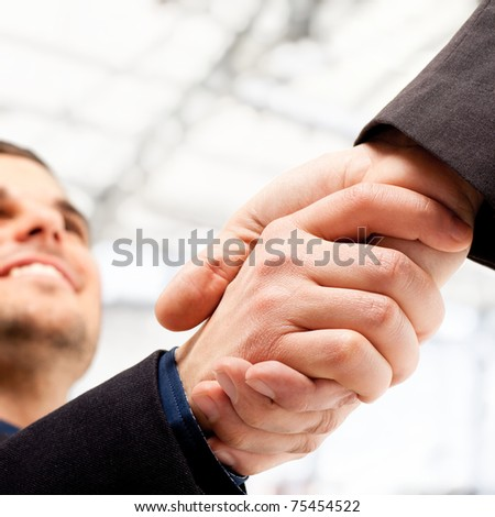 Business people shaking hands. Bright blurred background. - stock photo
