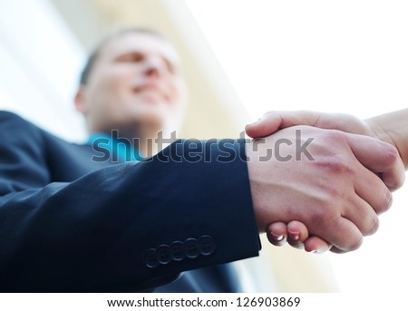 Business people shaking hands. Bright modern building background. Focus on hand. - stock photo