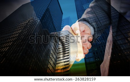 Business people shaking hands close up against low angle view of skyscrapers - stock photo
