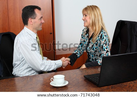 Business people shaking hands, coming to an agreement in the office. - stock photo