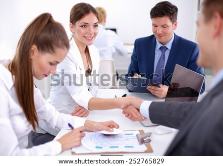 Business people shaking hands, finishing up a meeting, in office. - stock photo