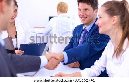 Business people shaking hands, finishing up a meeting, in office