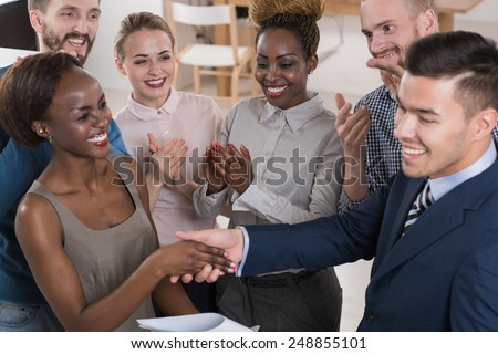 Business people shaking hands, finishing up a meeting multi-ethnic group of people - stock photo